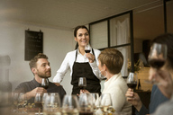 Smiling woman wearing apron holding wineglass with business people at table - MASF02805