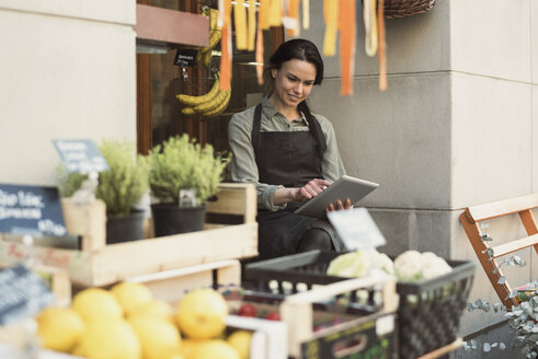 Smiling female owner using digital tablet while sitting at store entrance - MASF02814