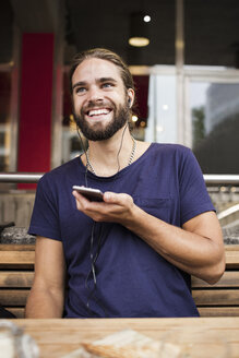 Smiling man listening music through smart phone while sitting at sidewalk cafe - MASF02823