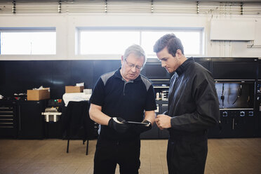 Senior mechanic and expert using digital tablet at auto repair shop - MASF02832