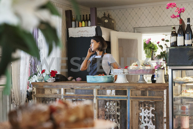 Serious woman talking on phone while standing by counter at cafe - MASF02835 - Maskot ./Westend61