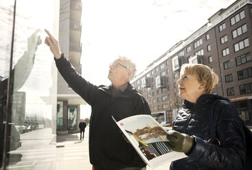 Senior woman reading catalog while man pointing on glass window in city - MASF02841