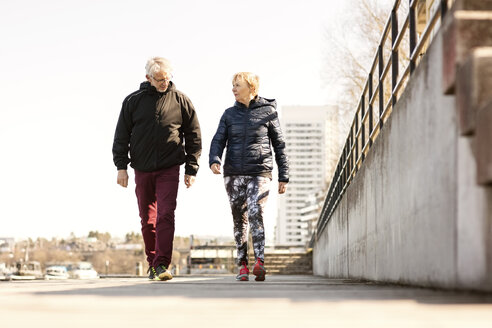 Senior couple in sportswear walking on sidewalk against clear sky - MASF02844