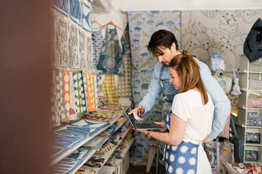 Serious owners using laptop in fabric shop - MASF02847