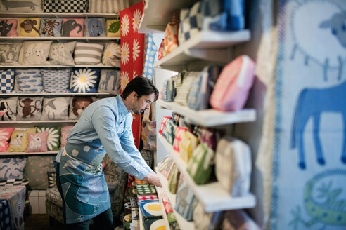 Side view of male owner arranging fabric on shelf at store - MASF02850