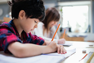 Serious students studying at desk in classroom - MASF02853
