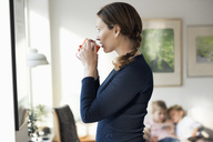 Side view of woman drinking coffee in living room at home - MASF02862