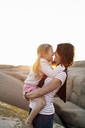 Side view of mother carrying daughter against clear sky during sunset - MASF02877