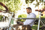 Side view of businessman using laptop while sitting on park bench - MASF02880