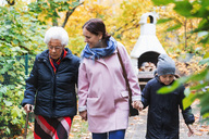 Senior woman walking with daughter and great grandson in park - MASF02889