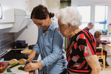 Side view of senior woman looking at daughter cutting zucchini in kitchen - MASF02892