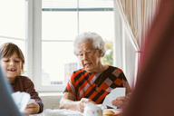 Senior woman playing cards with family at home - MASF02895