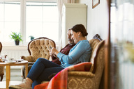 Side view of senior man using smart phone with daughter in living room - MASF02898