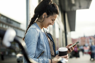 Side view of woman holding smart phone and coffee cup in city - MASF02901