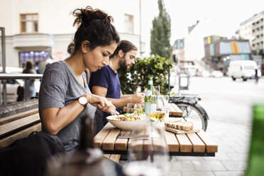 Side view of man and woman having lunch at sidewalk cafe in city - MASF02907