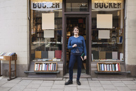 Portrait of happy woman holding book while standing outside bookstore - MASF02910