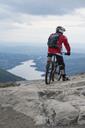 Rear view of mountain biker on rock against sky - MASF02913