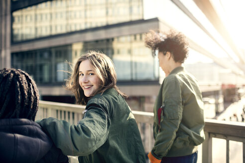 Portrait of smiling teenage girl walking with friends on bridge in city - MASF02916