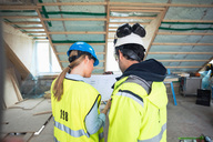 Rear view of male and female experts discussing at construction site - MASF02919