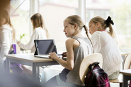 Rear view of girls sitting on desk against window in classroom - MASF02925