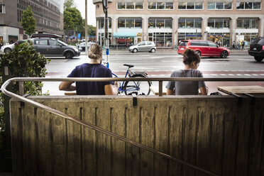 Rear view of man and woman sitting at sidewalk cafe in city - MASF02943