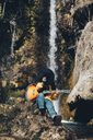 Spain, Lleida, young woman with guitar sitting on rock in front of waterfall covering face with hat - OCAF00177