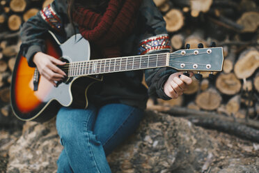 Young woman tuning guitar outdoors, partial view - OCAF00183
