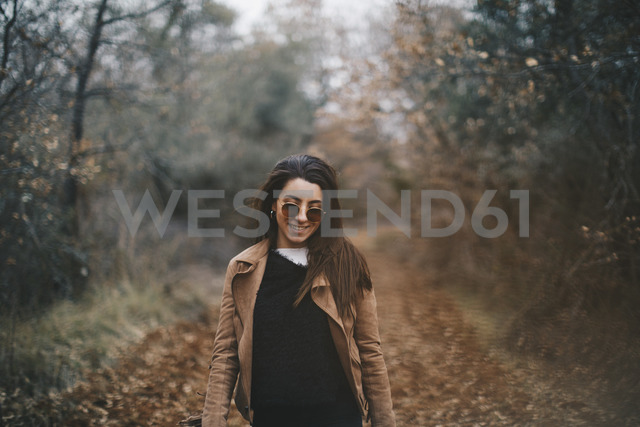 Portrait of smiling young woman in autumnal nature - OCAF00186