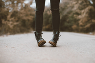 Woman wearing black boots, partial view - OCAF00195