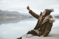 Smiling young woman sitting on jetty taking selfie with smartphone - OCAF00201