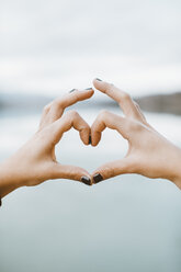 Woman's hands forming heart-shape in front of lake, close-up - OCAF00204