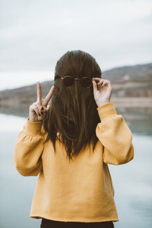 Funny 'portrait' of young woman with sunglasses showing victory sign - OCAF00207