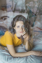 Portrait of smiling young woman lying on bed behind windowpane - KKAF00974