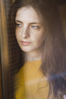 Portrait of pensive young woman with long brown hair looking out of window - KKAF00980