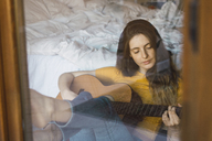 Portrait of relaxed young woman sitting behind windowpane playing guitar - KKAF00986