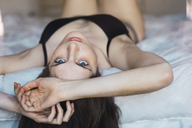 Young woman in underwear lying on bed - KKAF00989