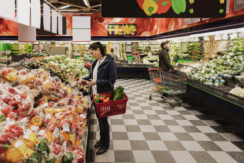 People buying groceries while standing in supermarket - MASF02959
