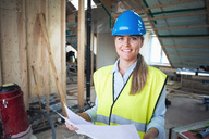 Portrait of confident manual worker analyzing document at construction site - MASF02974
