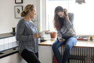 Mother talking with happy daughter using smart phone in kitchen - MASF02977