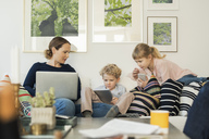 Mother and kids using technologies on sofa at home - MASF02980