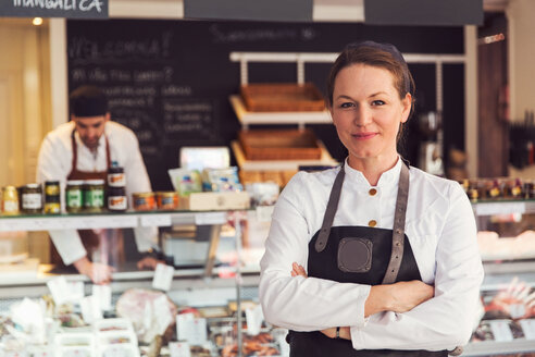 Portrait of confident owner standing arms crossed while colleague working in background at grocery store - MASF02986
