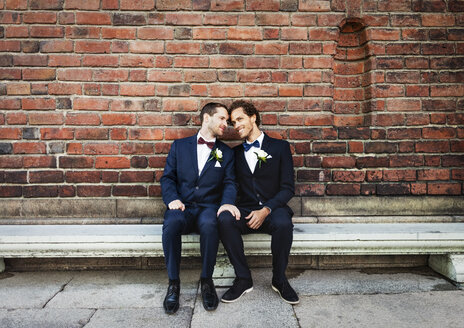 Newlywed gay couple sitting on bench against brick wall - MASF02992