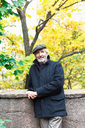 Portrait of confident senior man leaning on retaining wall while standing in park during autumn - MASF03001