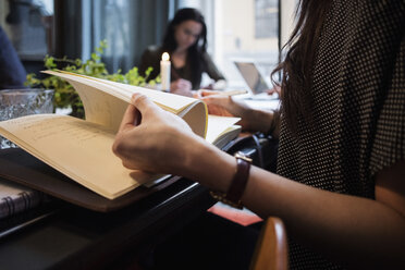 Midsection of woman turning pages sitting at table in creative office - MASF03008