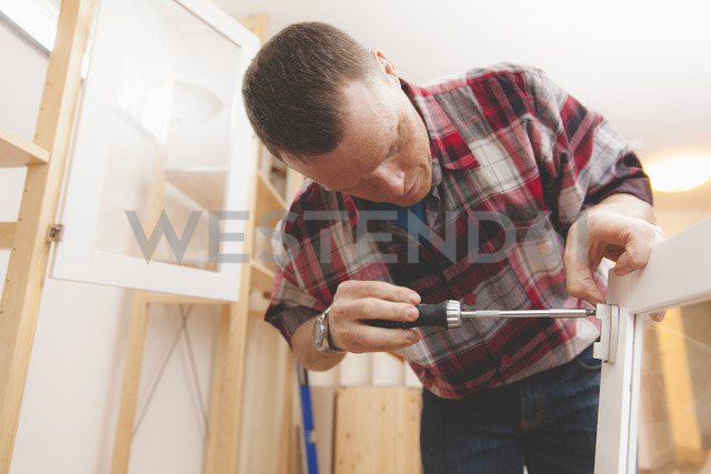 Mature man using screwdriver on cabinet door at home - MASF03011