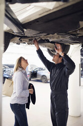 Mechanic with female customer standing under car at repair shop - MASF03014