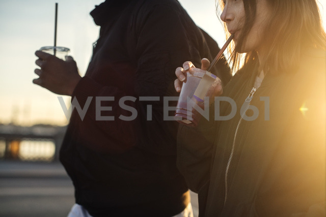 Midsection of friends drinking juice while walking in city - MASF03017