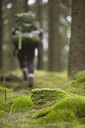 Mossy rocks in forest with hiker walking in background - MASF03026