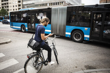 Man with bicycle using mobile phone while standing on city street against articulated bus - MASF03041