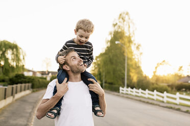 Happy father carrying son on shoulders while standing at street against clear sky - MASF03050